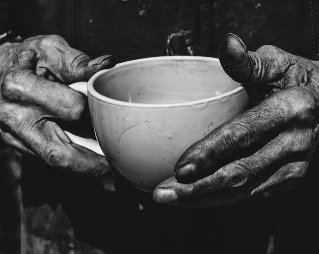 Старший мужчина держит чашку чая в руках