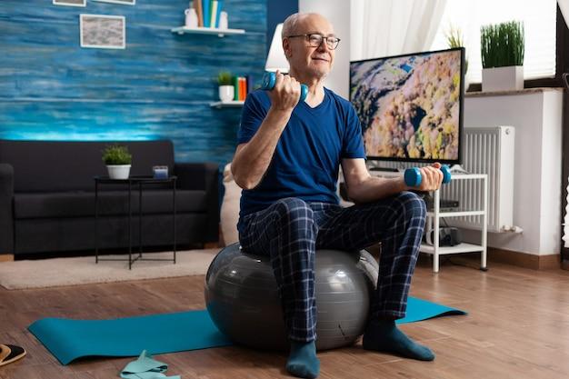 腕をしているダンベルを持っている年配の男性は、筋肉の抵抗を訓練するストレッチ体の筋肉を行使します