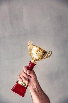 황금 트로피를 손에 들고 수석 남자입니다. 승리와 성공 개념