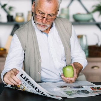 Senior man holding green apple in hand reading newspaper