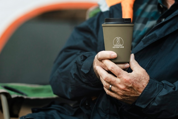 Senior man holding green reusable cup