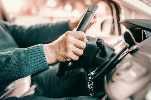 Старший мужчина, держась за руки на рулевое время и вождение своего автомобиля.