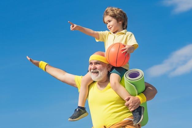 Старший мужчина держит внука на плечах