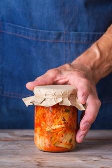 木製のテーブルの上のガラスの瓶に自家製の有機伝統的な韓国のキムチキャベツサラダを手に持っている年配の男性。発酵菜食主義者、ビーガン保存腸健康食品の概念