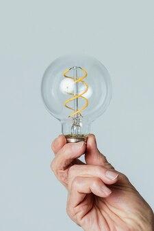 Senior man holding a light bulb against a blue background