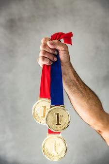 메달을 손에 들고 수석 남자입니다. 승리와 성공 개념