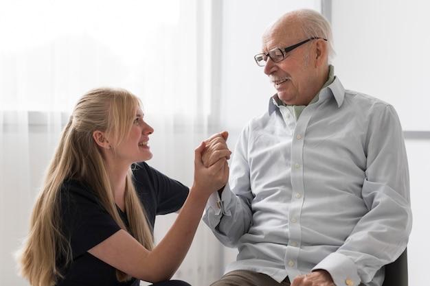 看護師の手を握って年配の男性