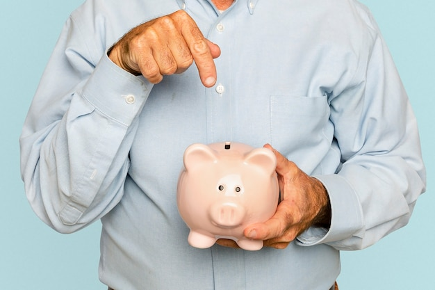 Senior man holding piggy bank for financial savings campaign