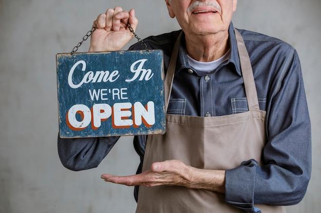 Старший мужчина держит табличку с вывеской магазина, заходите, мы открыты