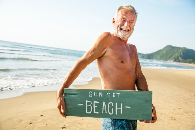 Senior man holding a signboard at the beach