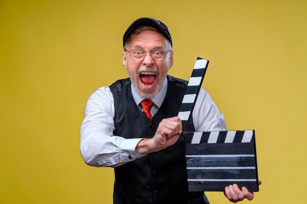 Старший мужчина держит заслонку пленки крупным планом. режиссура фильма. производство фильма. человеческие эмоции. человек с заслонкой фильма во время съемок
