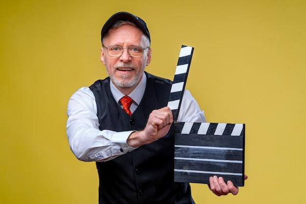 Senior man holds film flap close up. film directing. film production. human emotions.