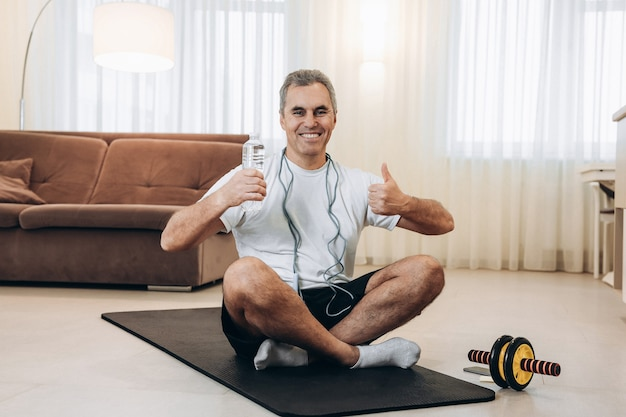 Senior man holds water bottle, smiles with teeth, sits on black yoga map and thumbs up
