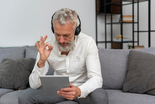 Senior man at home on the couch having a video call on tablet and wearing headphones