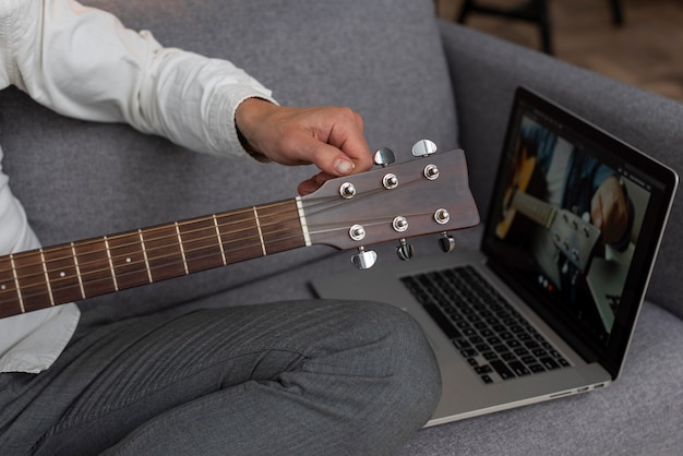 Senior man at home on the couch using laptop to study guitar lessons