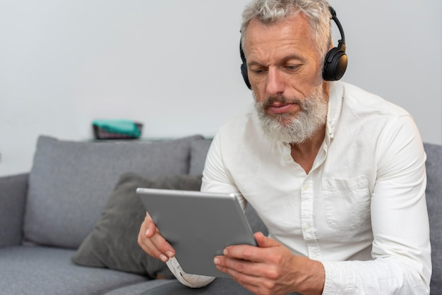 Senior man at home on the couch using tablet device and headphones