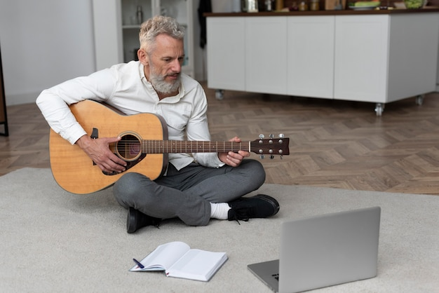 Senior man at home on the floor taking guitar lessons
