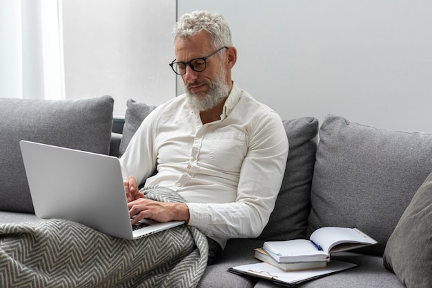 Senior man at home studying on the couch using laptop
