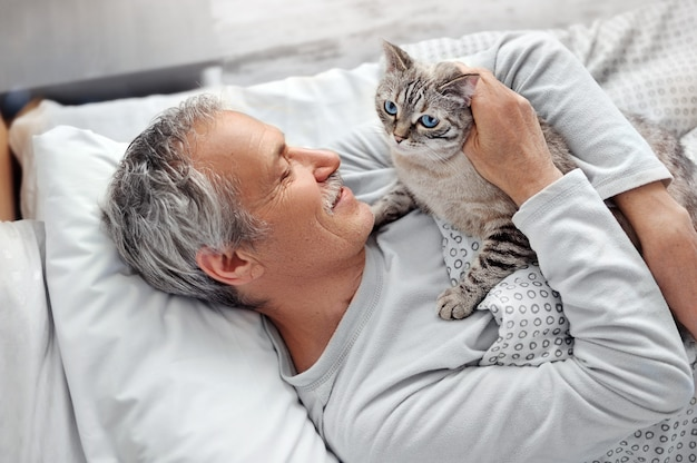 Старший мужчина обнимает кота в постели