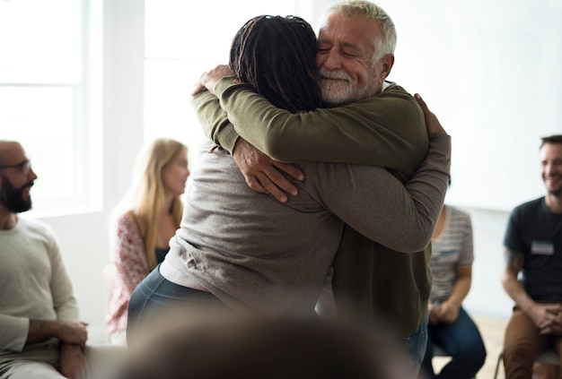 Senior man hugging woman in support group