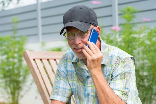 Старший мужчина в бейсболке портрет с помощью смартфона