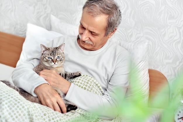 Старший мужчина в спальне держит в руках полосатого кота