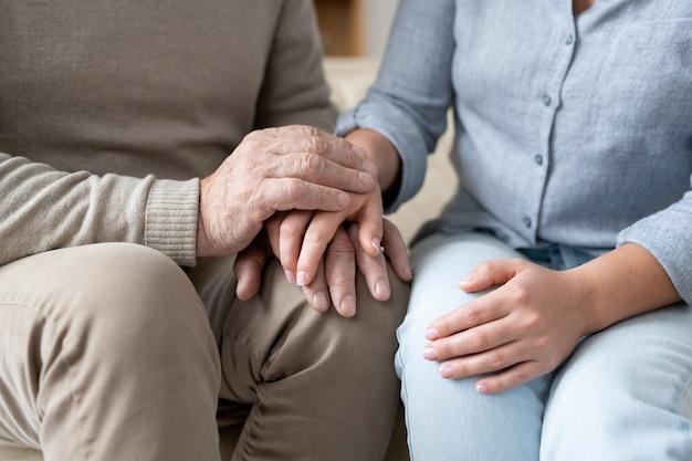 Старший мужчина в повседневной одежде держит руку на руке своей маленькой дочери, пока оба сидят рядом