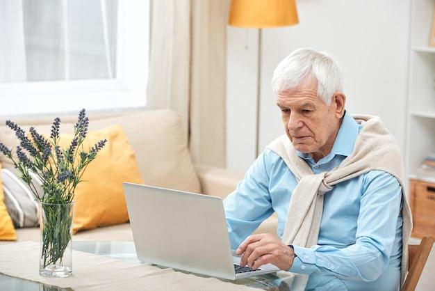 ネットサーフィンをしながら自宅でオンライン情報を探している間、ラップトップの前のテーブルのそばに座っているカジュアルウェアの年配の男性