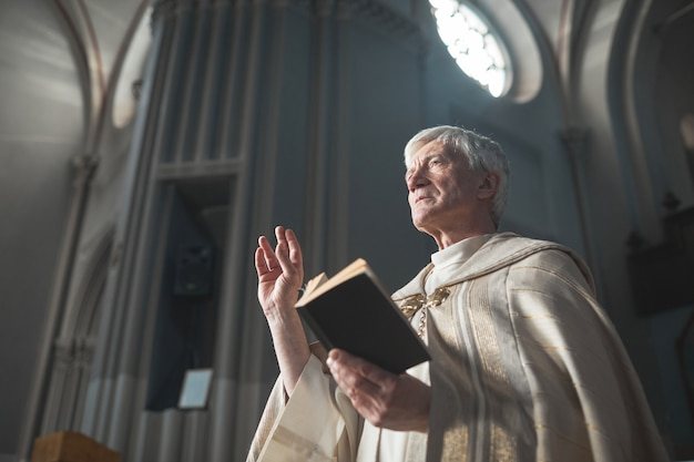 教会で奉仕しながら聖書を読んでいる衣装を着た年配の男性