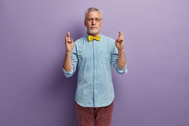 Старший мужчина в джинсовой рубашке и желтом галстуке-бабочке