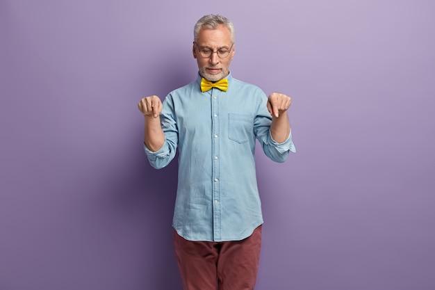 デニムシャツと黄色の蝶ネクタイの年配の男性