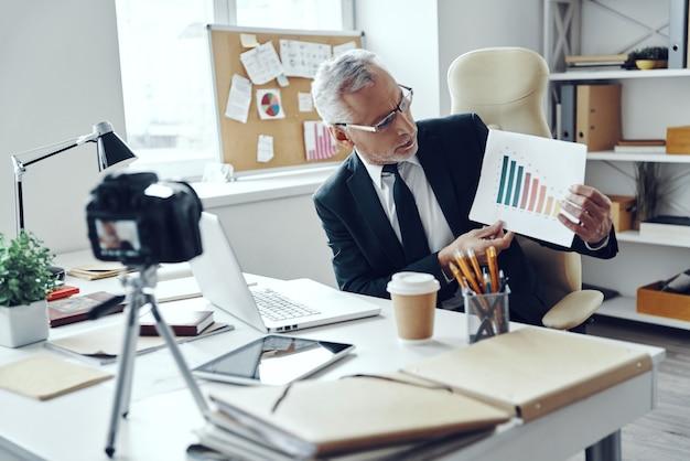 ソーシャルメディアビデオを作成しながらチャートを示すエレガントなビジネススーツの年配の男性