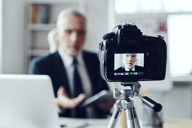ソーシャルメディアビデオを作成しながらデジタルタブレットを使用してエレガントなビジネススーツの年配の男性