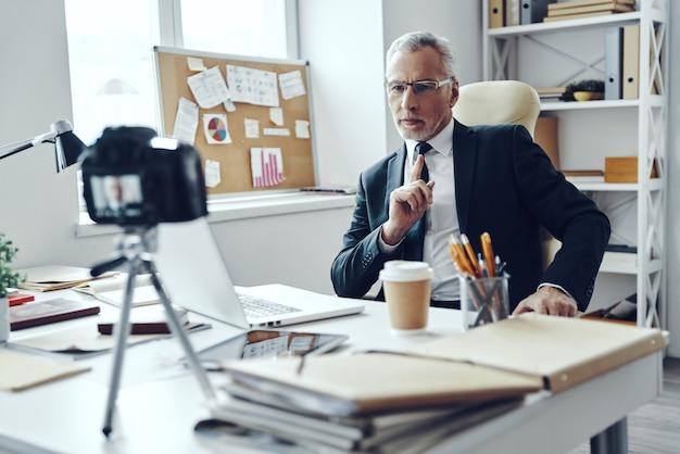 ソーシャルメディアビデオを作成しながらラップトップを使用して作業するエレガントなビジネススーツの年配の男性
