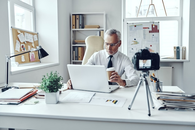 ソーシャルメディアビデオを作成しながらラップトップを使用して作業しているエレガントなシャツとネクタイの年配の男性