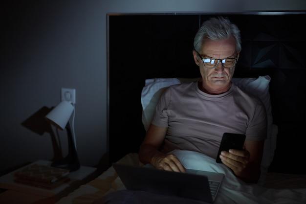 안경에 수석 남자가 침대에 누워서 늦게까지 일하는 온라인 작업에서 자신의 휴대 전화와 노트북을 사용