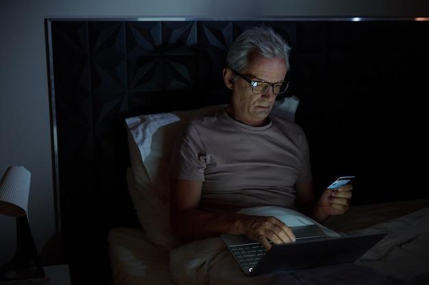 彼のベッドに横たわって、寝室でラップトップを使用してクレジットカードでオンラインで支払う眼鏡の年配の男性