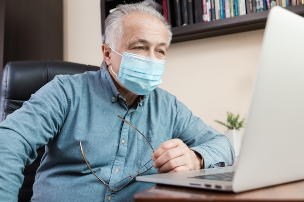 Старший мужчина в маске работает или общаться на ноутбуке дома. учеба, обучение, работа, общение, развлечения, отдых в период коронавируса.