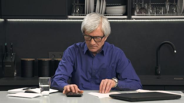眼鏡の年配の男性は電卓の費用を考慮します