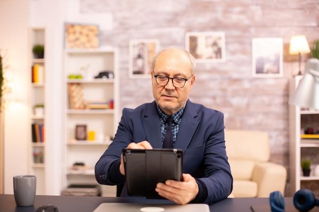 아늑한 집에서 현대적인 디지털 태블릿을 사용하는 60대 노인