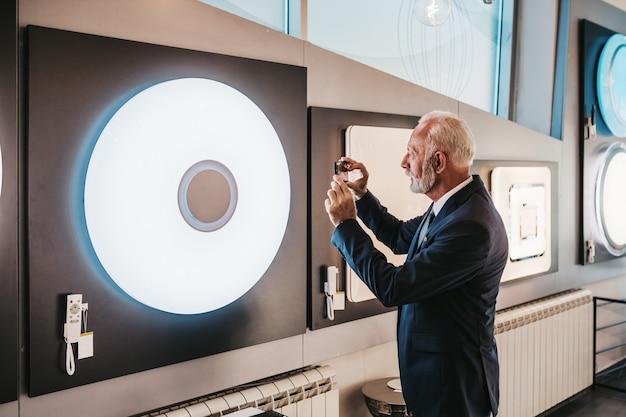 Старший мужчина в магазине домашнего освещения снимает люстра для своего дома