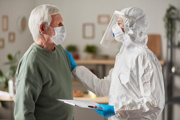 訪問中のコロナウイルスワクチン接種について保護服を着た医師と相談するマスクの年配の男性