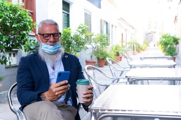 コロナウイルスの発生時にカフェで現代の電話とマスクの年配の男性