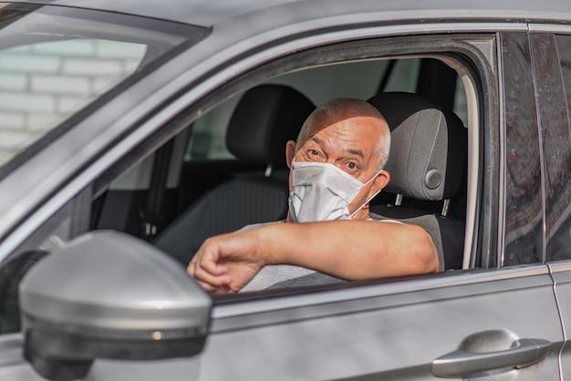 カメラを見ながら、車を運転する医療マスクの年配の男性。