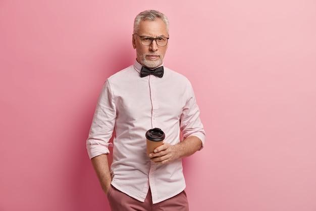 Старший мужчина в розовой рубашке и черном галстуке-бабочке держит чашку кофе