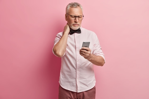 Старший мужчина в розовой рубашке и черном галстуке-бабочке держит телефон