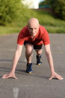 走る準備ができている位置にいる年配の男性。スプリントの準備ができている決心した男。健康的なライフスタイルと運動のスタートアップの概念