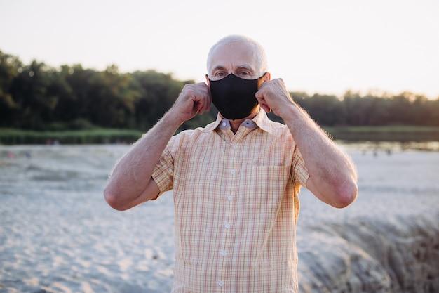 Старший мужчина в защитной маске респиратор, вспышка вирусной болезни коронавируса covid-2019