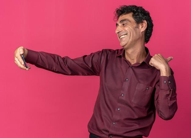 Старший мужчина в фиолетовой рубашке делает селфи с помощью смартфона, счастливый и позитивный, весело улыбаясь, стоя на розовом фоне