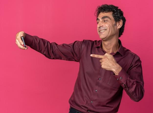 행복하고 긍정적 인 분홍색 위에 유쾌하게 서있는 스마트 폰을 사용하여 셀카를하고 보라색 셔츠에 수석 남자